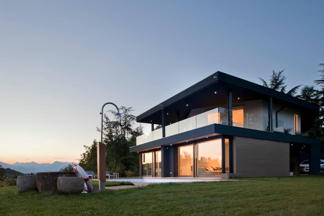 il soggiorno e la sala da pranzo si affacciano sul lato sud ovest dove c'è la  piscina : Case in stile  di iarchitects