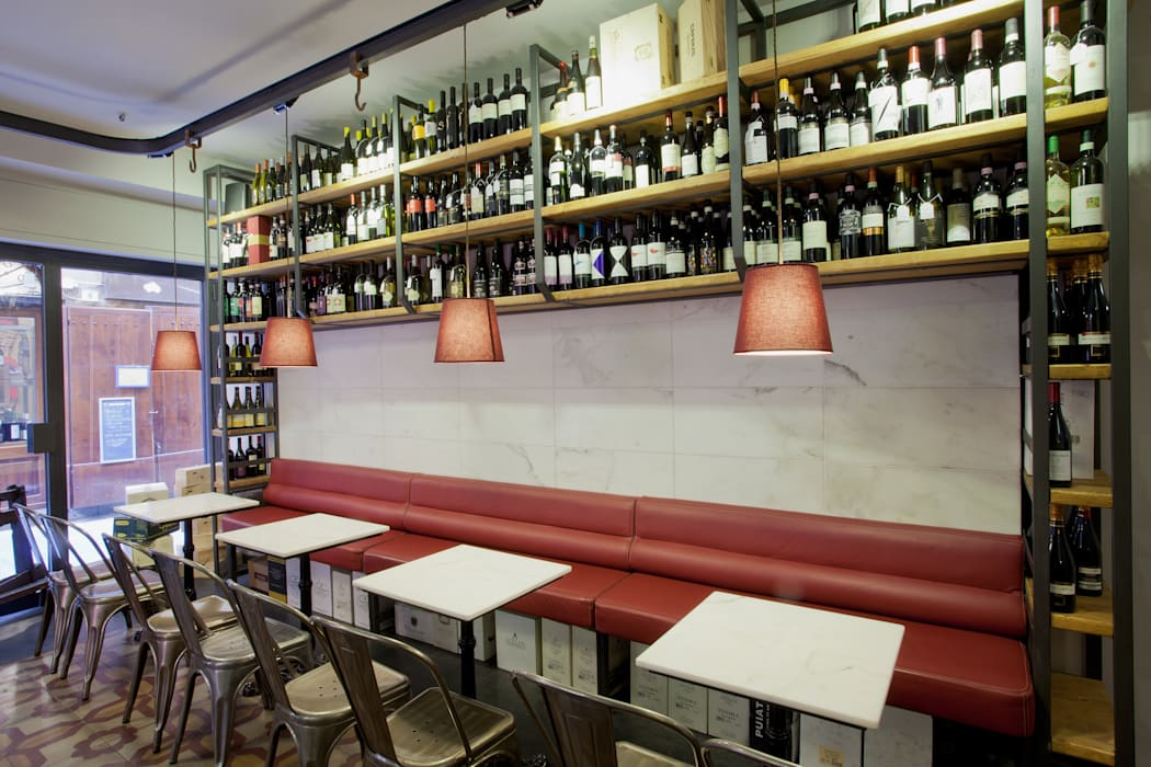 Le sedute e l'esposizione dei vini: Bar & Club in stile  di Manrico Mazzoli Architetto