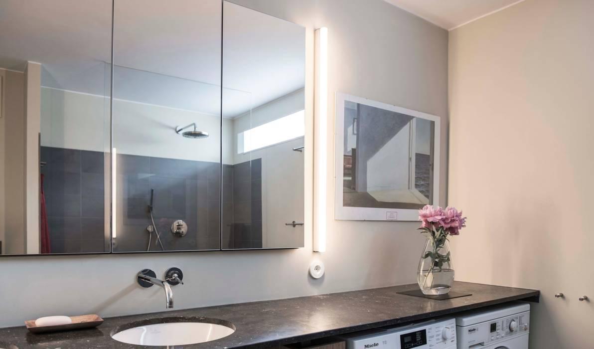 Wastafelblad van hardsteen en verlichting naast de spiegel:  Bathroom by B1 architectuur