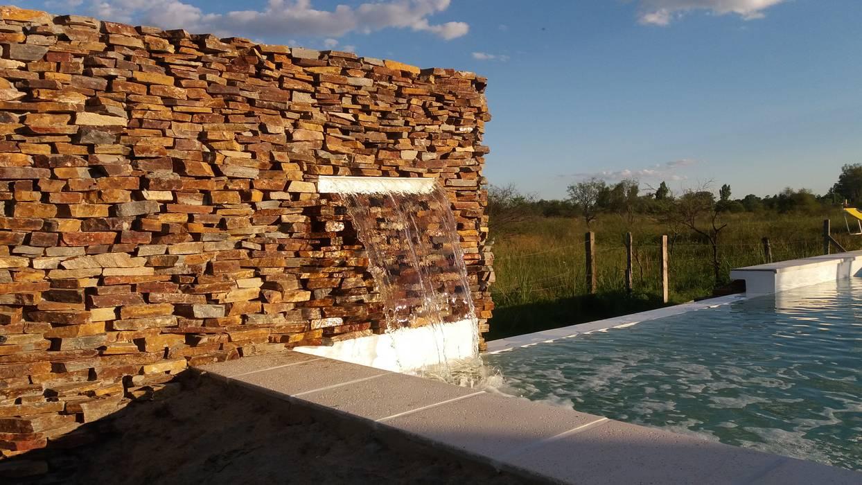 Plano piedra con cascada: Piletas de estilo  por VHA Arquitectura