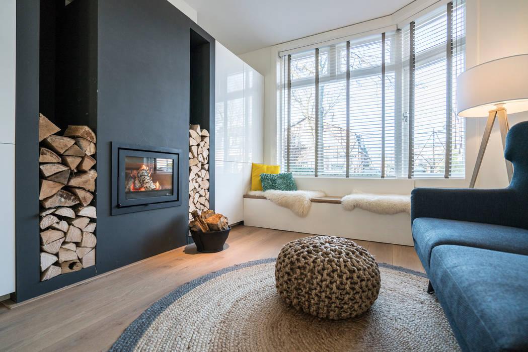 Houtkachel met houtvoorraad bij de erker:  Woonkamer door Masters of Interior Design