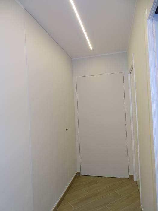 Corridoio con avanderia ed armadio a muro mimetizzati: Ingresso & Corridoio in stile  di NicArch