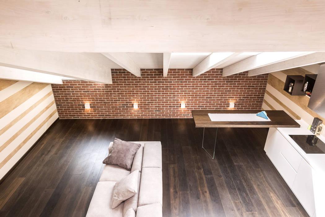 Il calore di una mansarda ristrutturata con i mattoni faccia a vista Genesis: Soggiorno in stile in stile Moderno di B&B Rivestimenti Naturali