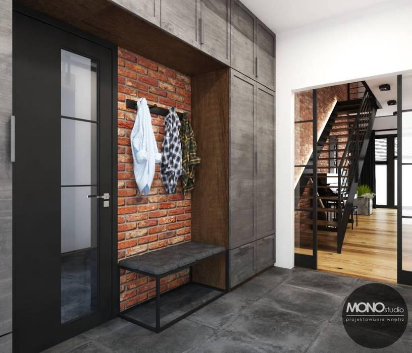 Przedpokój z elementem cegły Industrialny korytarz, przedpokój i schody od MONOstudio Industrialny