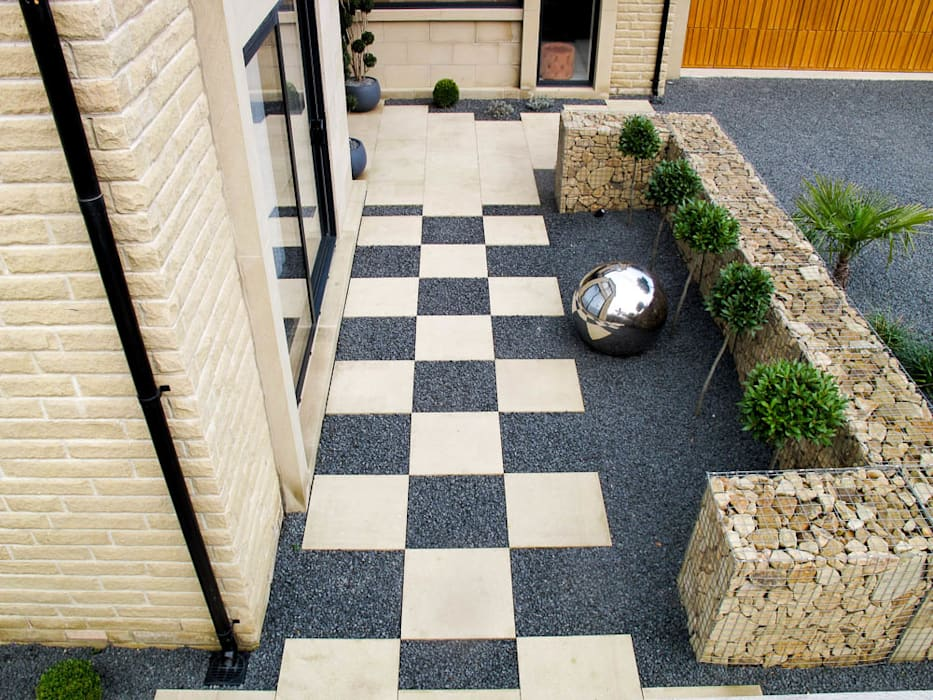 Checkerboard paving and futuristic garden feature:  Garden by Yorkshire Gardens