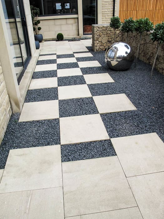 Checkerboard paving and stainless steel ornament:  Garden by Yorkshire Gardens