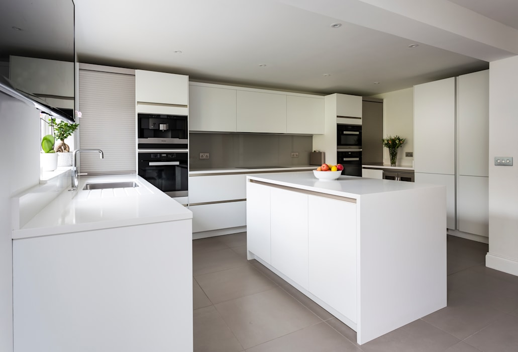 White contemporary kitchen in Hertfordshire by John Ladbury and Company.:  Kitchen by John Ladbury and Company