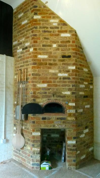wood-fired oven enclosed in reclaimed red bricks:  Kitchen by wood-fired oven