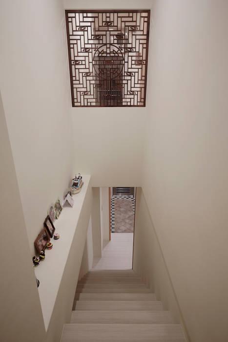 久具歷史的窗花特地被要求一定要保留下來,當房間內拉門拉起也把戶外的光線引進梯間:  走廊 & 玄關 by 弘悅國際室內裝修有限公司,