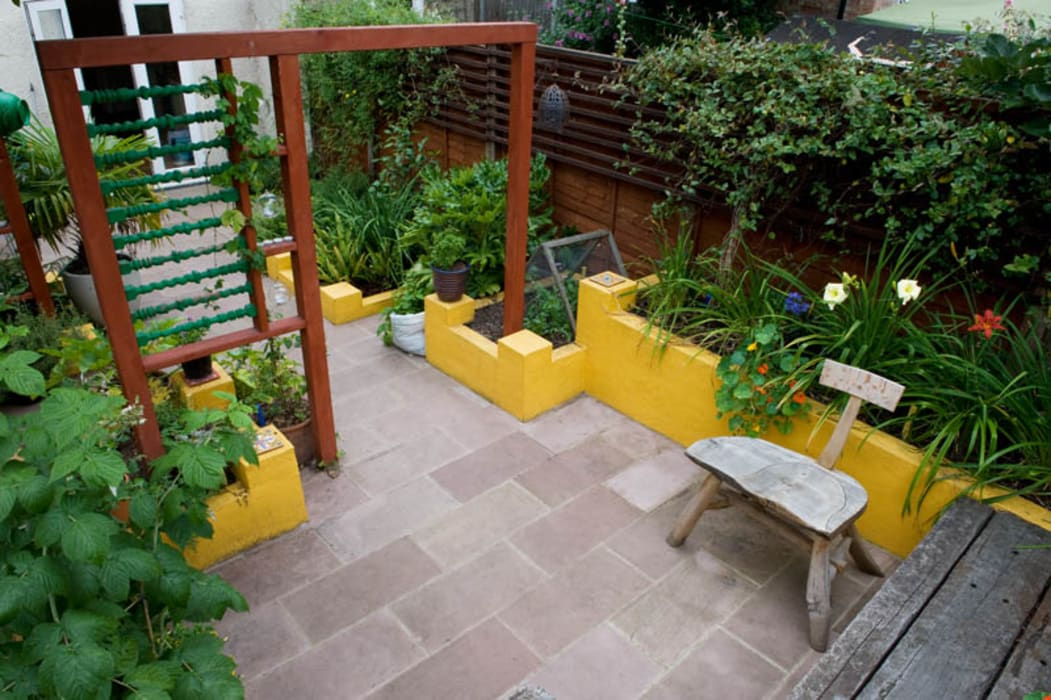 Raised planters and sandstone patio:  Garden by Earth Designs