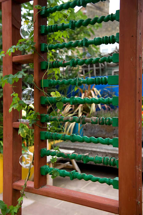 Reclaimed spindles set into garden screen:  Garden by Earth Designs