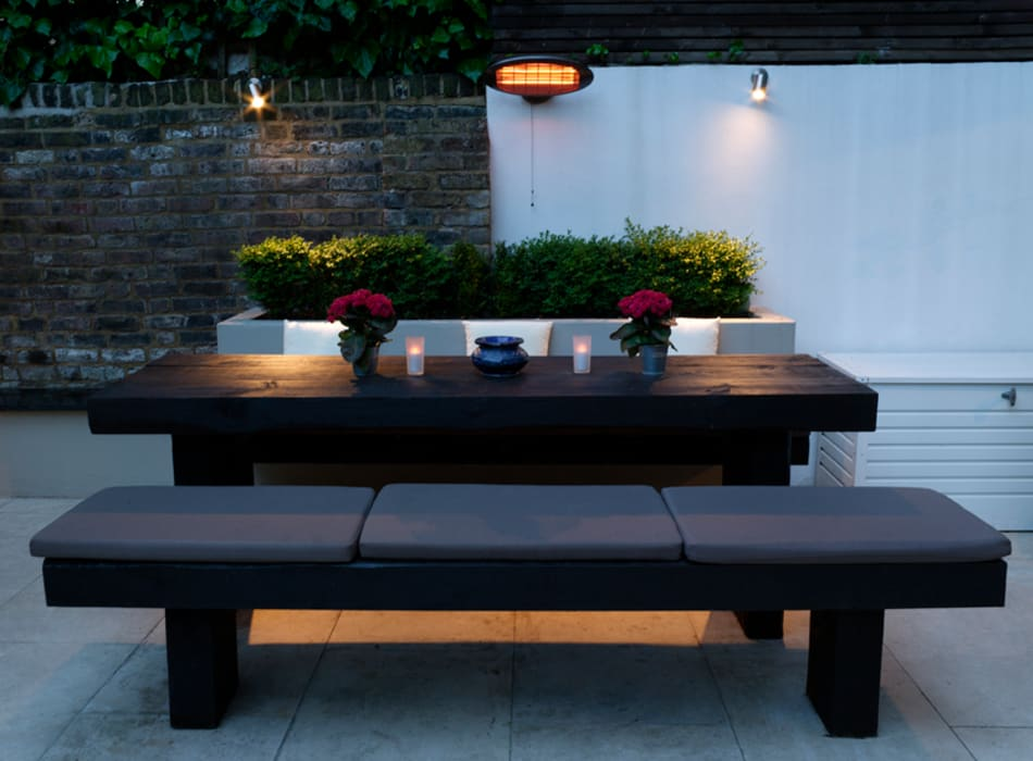 Dining area by night:  Garden by Earth Designs