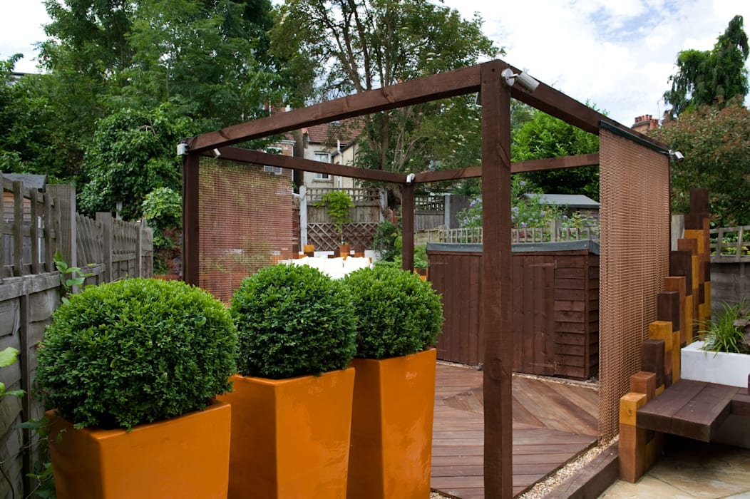 Fibreglass planters, pergola and hidden bike store:  Garden by Earth Designs
