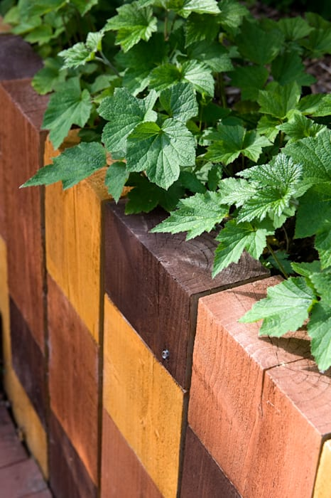 Railway sleeper wall with trio of stained blocks:  Garden by Earth Designs