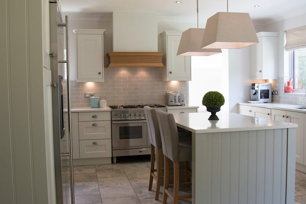 The kitchen island has seating for two, as well as much needed extra work space:  Built-in kitchens by ADORNAS KITCHENS