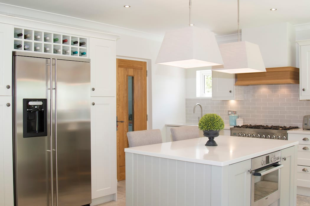 Wine racks were added above the fridge to maximise storage:  Built-in kitchens by ADORNAS KITCHENS