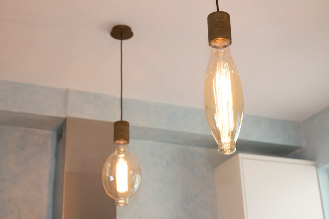 Filament bulbs above the kitchens island add ambience:  Built-in kitchens by ADORNAS KITCHENS