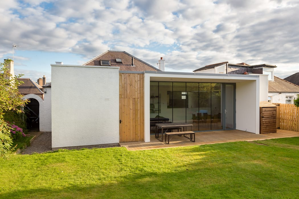 The timber cladding extends up the wall to form a door into the garden store.:  Detached home by Capital A Architecture