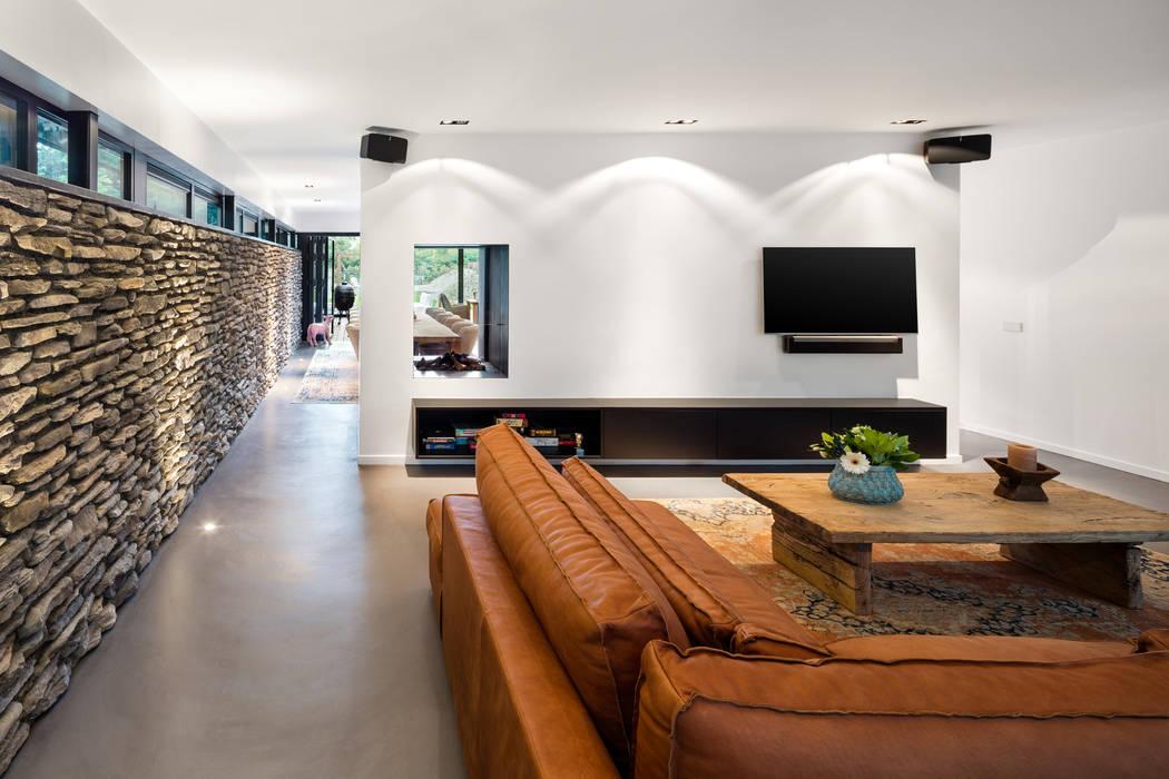 Bosrijk wonen in een droomvilla:  Woonkamer door BNLA architecten