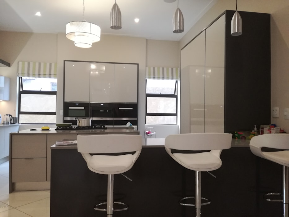 high gloss grey doors with grey counter tops and charcoal grey mat:  Built-in kitchens by Première Interior Designs, Modern
