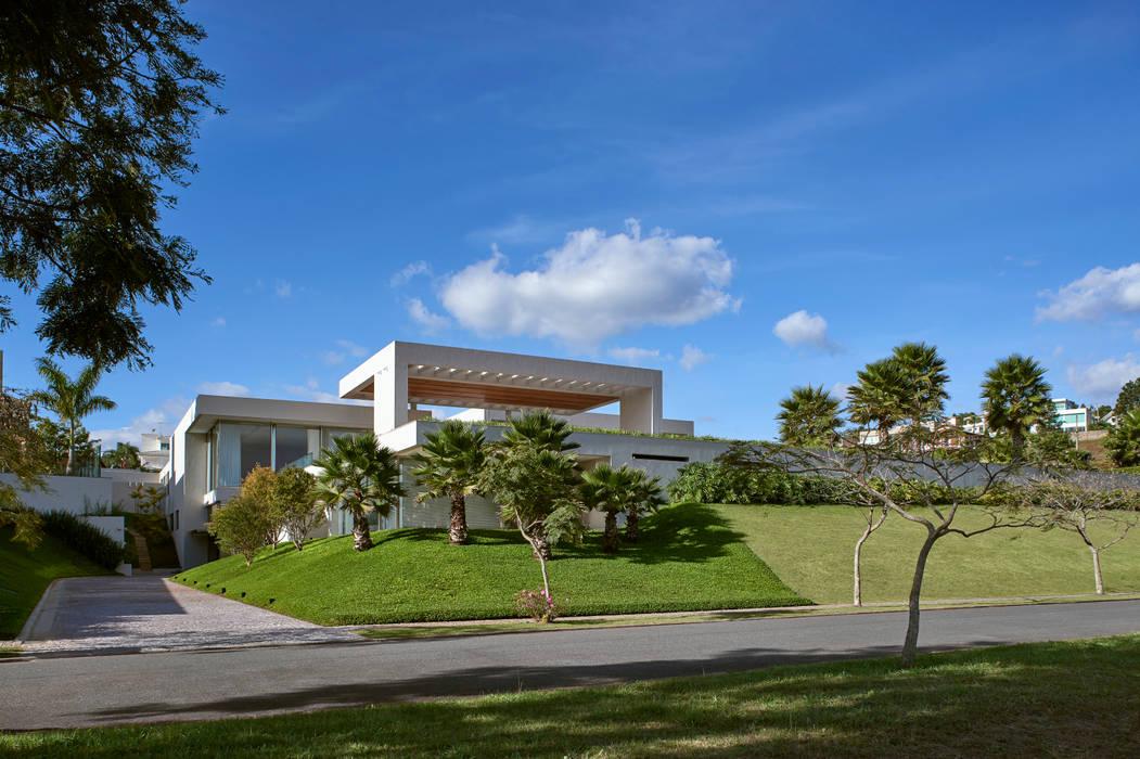 Perfeita integração dos volumes da edificação com os amplos jardins e o entorno.: Casas familiares  por Lanza Arquitetos