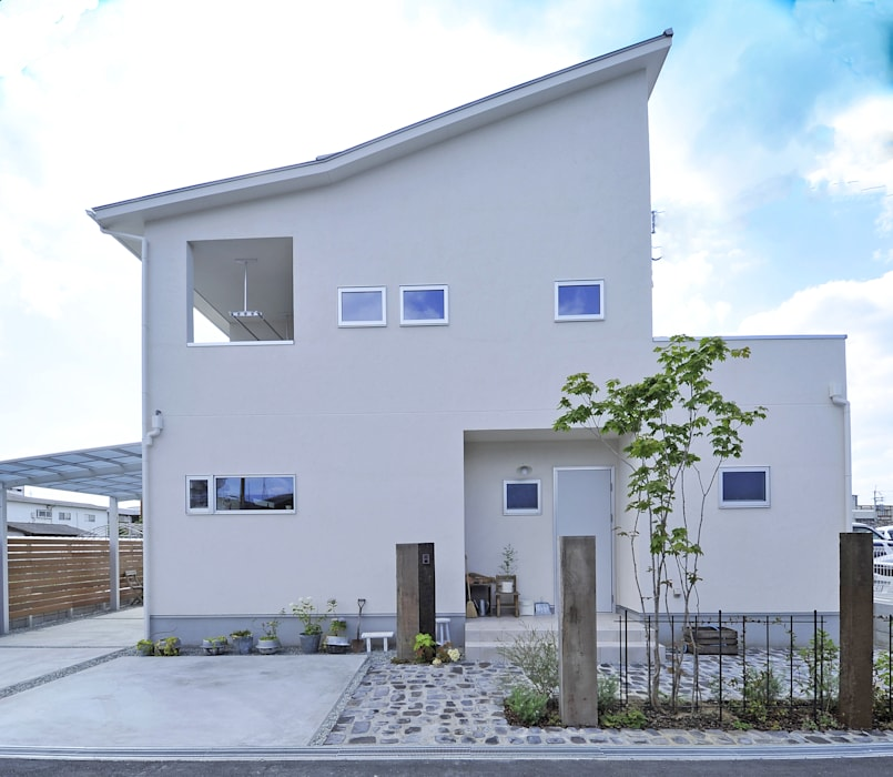 白い壁にあふれる緑がさわやかな印象を与える外観: タイコーアーキテクトが手掛けた一戸建て住宅です。