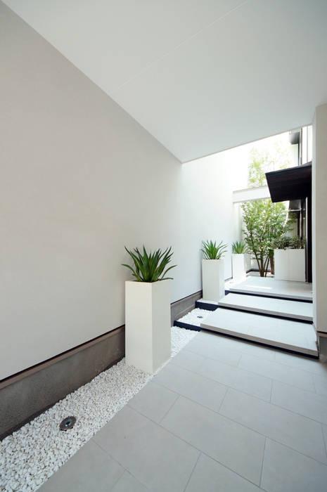 壁と建物にかこまれたアプローチの演出: TERAJIMA ARCHITECTSが手掛けた庭です。,
