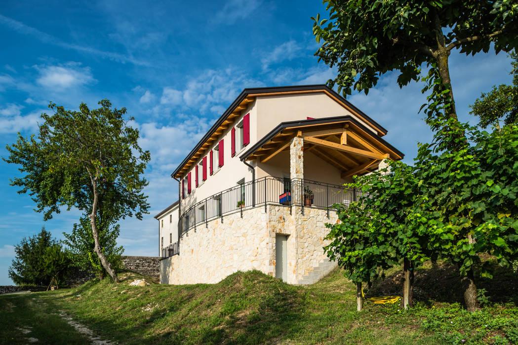 Stile collinare: Casa di legno in stile  di Woodbau Srl