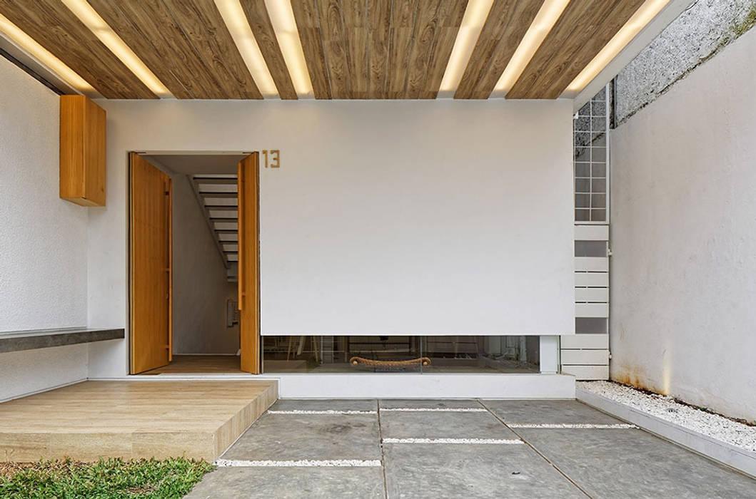 Mặt tiền ngôi nhà được thiết kế mặt kính lớn kéo dài xuống tận đáy.:  Cửa nhà để xe by Công ty TNHH Thiết Kế Xây Dựng Song Phát