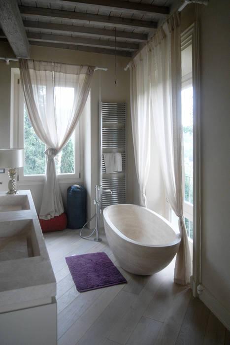 Bagno con rivestimenti, lavabo e vasca in travertino: Bagno in stile  di Pietre di Rapolano