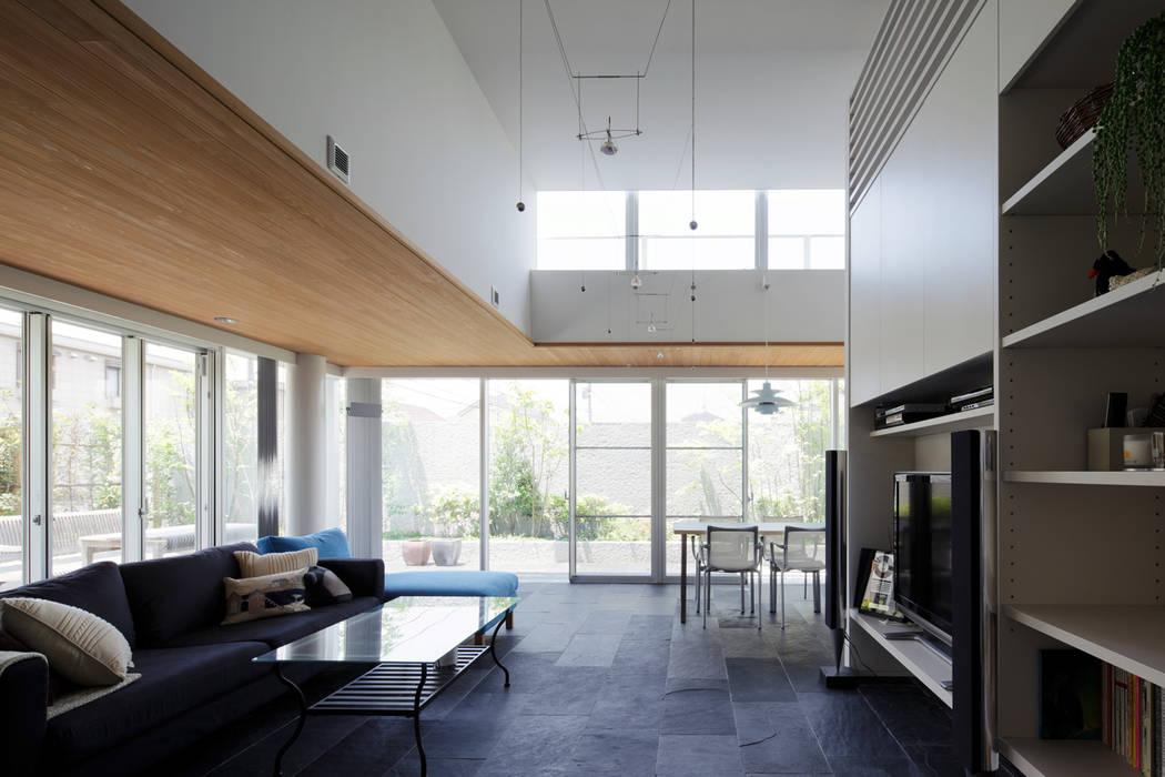 ミドセンチュリーテイスト 居間がテラスと一体化して繋がる成城の住まい: JWA,Jun Watanabe & Associatesが手掛けたリビングです。,