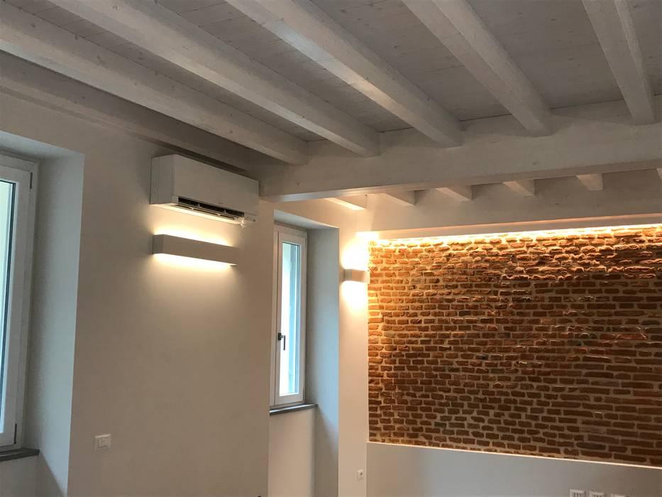 Scorcio parete soggiorno con mattoni pieni: Soggiorno in stile in stile Classico di Cozzi Arch. Mauro