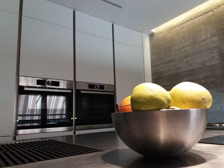 Cucina con isola in vetro e colonne laccato bianco: Cucina attrezzata in stile  di Formarredo Due design 1967