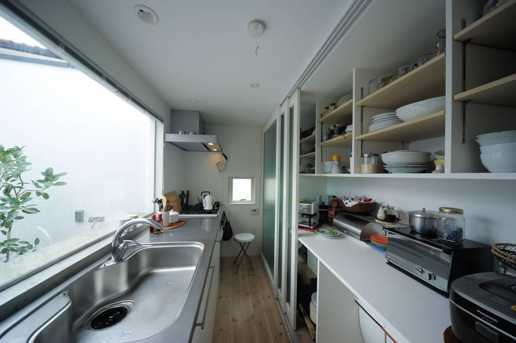 キッチン背面パントリー: 石川淳建築設計事務所が手掛けたシステムキッチンです。
