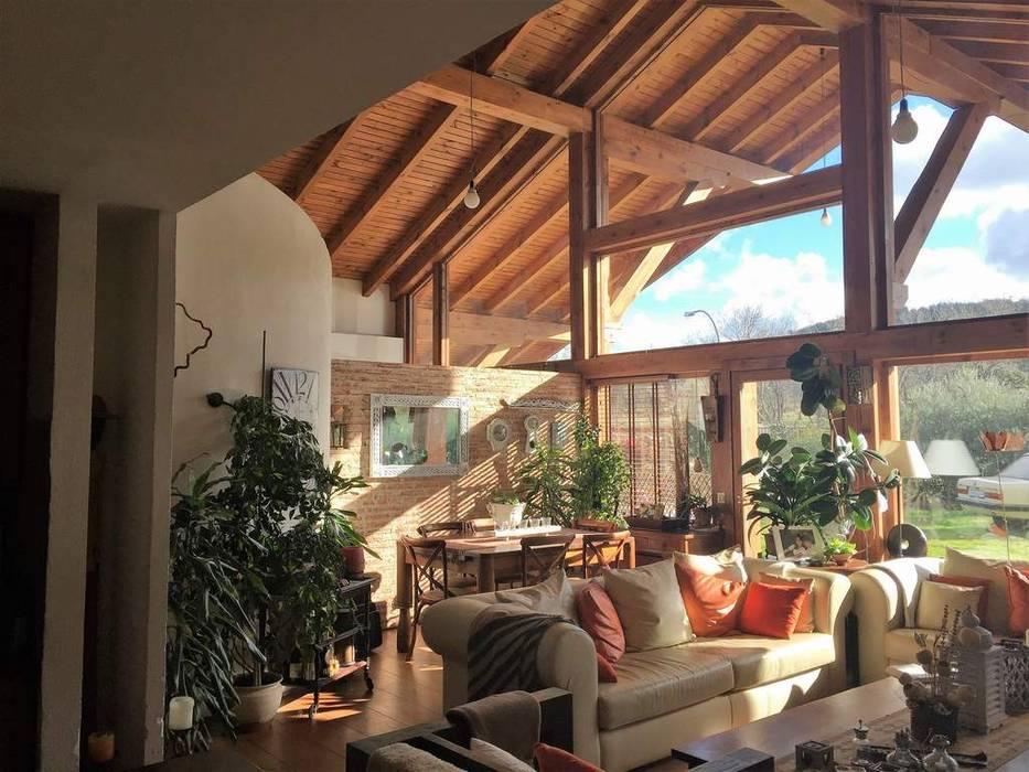 La casa del tejado hasta el suelo. Becerril de la Sierra, Madrid: Salones de estilo  de Manuel Monroy Pagnon, arquitecto