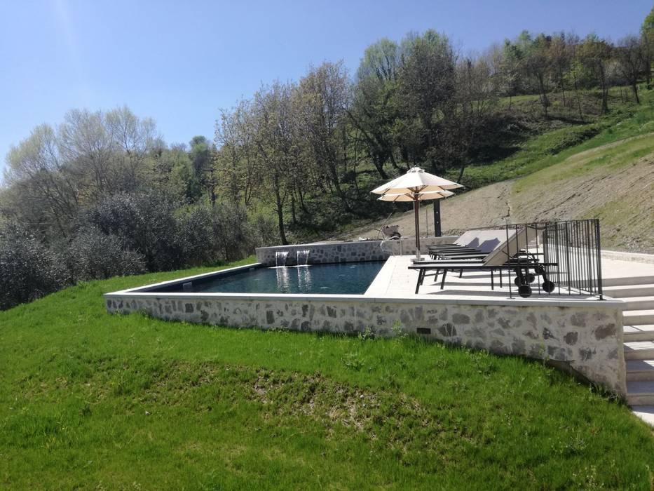 Una casa immersa nel verde con una stupenda piscina .: Giardino con piscina in stile  di Aquazzura Piscine