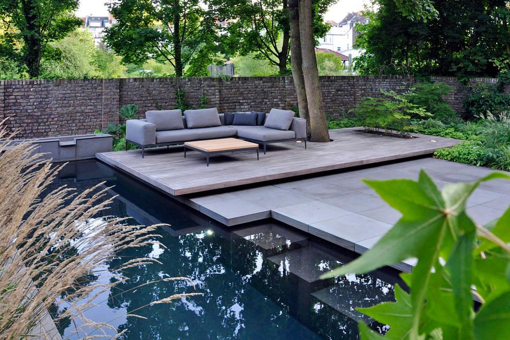 Swimming Pool mit schwebendem Sitzplatz vor einer historischen Gartenmauer unter einem Großbaum:  Garten von Terramanus Landschaftsarchitektur