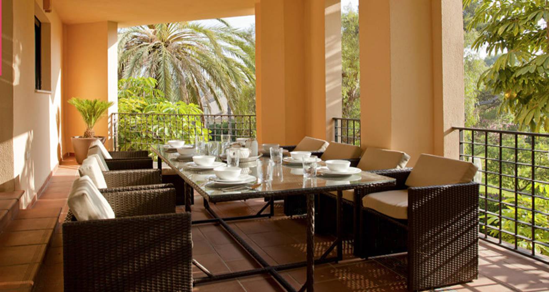 Terraza decorada con un juego de mesa y sillas de mimbre: comedores ...