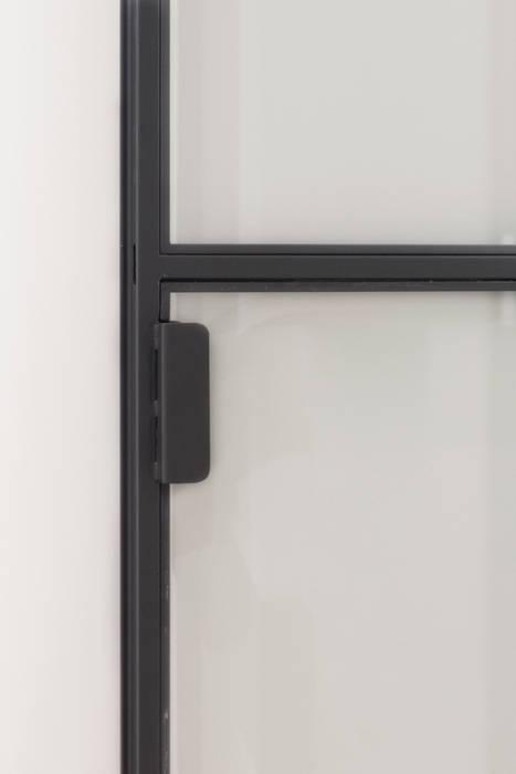Dettaglio della porta a vetri e della maniglia di PLUS ULTRA studio Minimalista Ferro / Acciaio