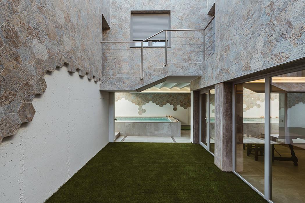 Uno de los cuatro patios de la casa. de OOIIO Arquitectura Moderno Cerámico
