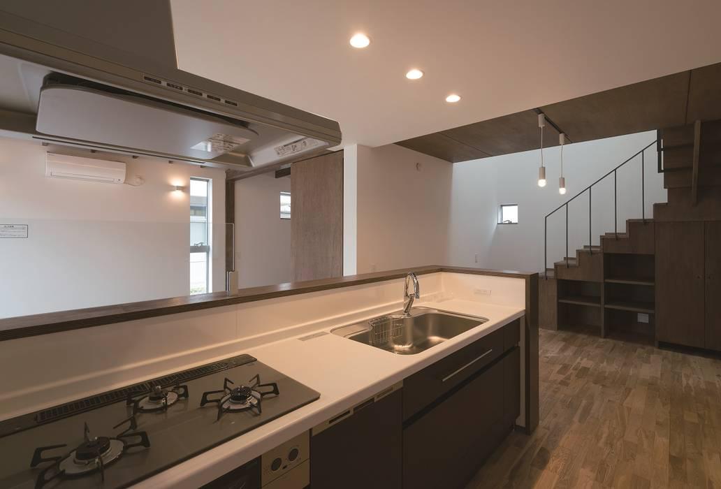 キッチンからダイニングとリビングを見る: 三浦尚人建築設計工房が手掛けたシステムキッチンです。,モダン 木材・プラスチック複合ボード