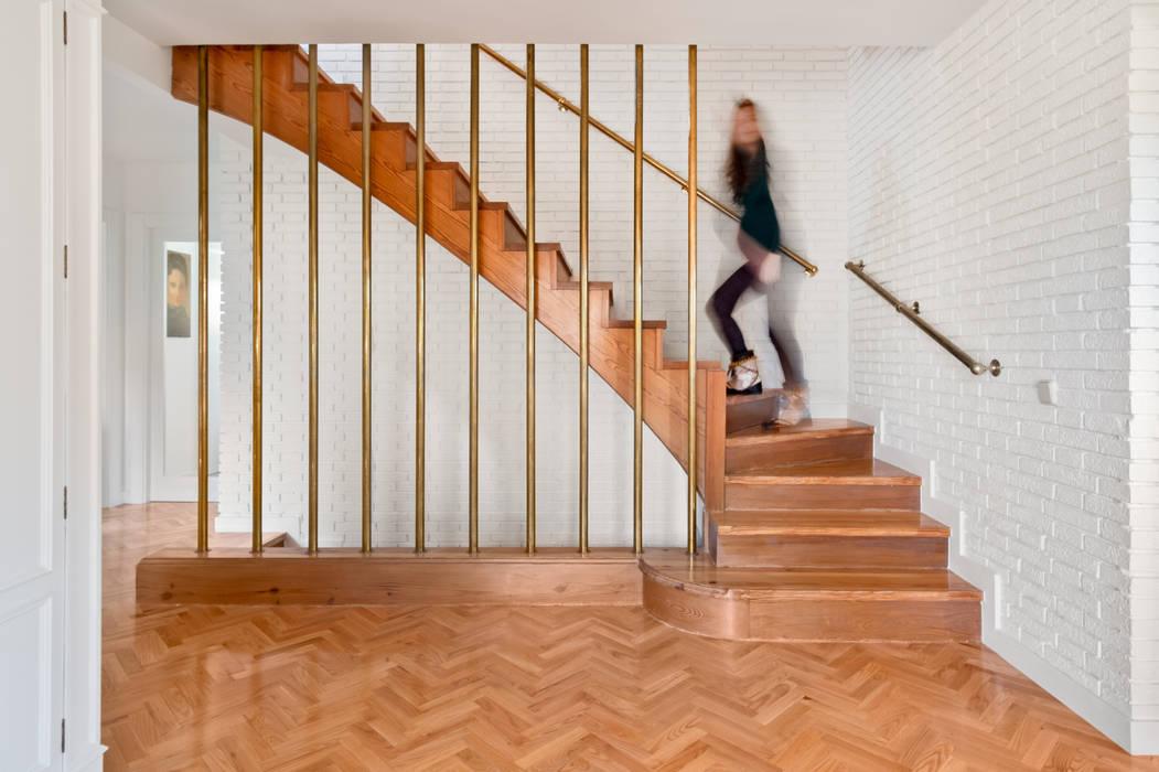 Hall de entrada y escalera de acceso a la primera planta: Escaleras de estilo  de Arquigestiona Reformas S.L., Moderno