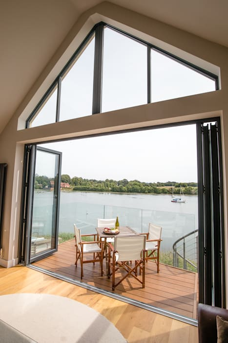 View of high-level window, bi-folding doors and balcony from living room Ruang Keluarga Modern Oleh dwell design Modern