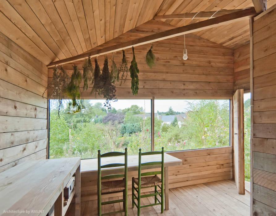 Gartenblick aus dem gemütlichen, modernen Innenraum aus Holz:  Gartenhaus von AMUNT Architekten in Stuttgart und Aachen,Landhaus