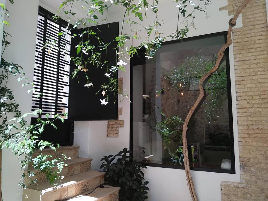 Vista del ventanal y reja de salida al callejón Balcones y terrazas de estilo rústico de Gestionarq, arquitectos en Xàtiva Rústico Aluminio/Cinc