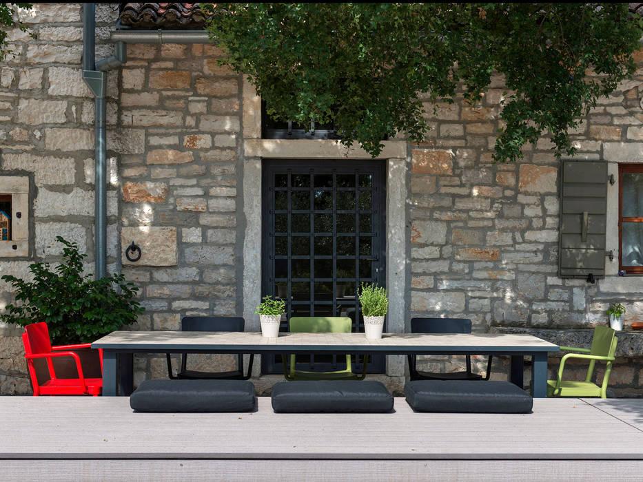 Sitzfläche mit grauen Premium WPC Massivdielen vor Natursteinhaus im Landhausstil Balkon, Veranda & Terrasse im Landhausstil von MYDECK GmbH Landhaus Holz-Kunststoff-Verbund