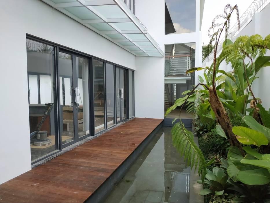 Teras samping ruang keluarga Havia Architecture Studio Balkon, Beranda & Teras Tropis