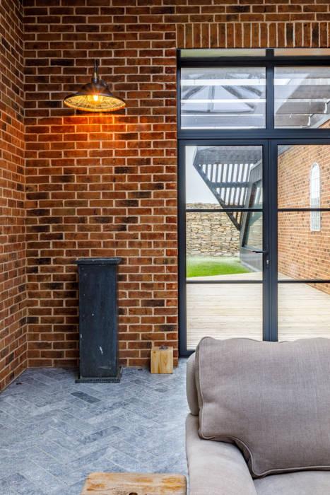 Internal brickwork and retro lighting beside art deco style windows Arco2 Architecture Ltd Pintu & Jendela Modern