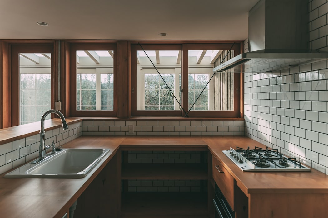 キッチン、奥にサンルーム の 株式会社シーンデザイン建築設計事務所 オリジナル
