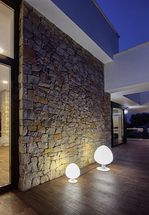 Vista del muro de piedra natural de la terraza - Iluminación de exterior - Casa Gerard - Chiralt Arquitectos Balcones y terrazas de estilo moderno de Chiralt Arquitectos Moderno
